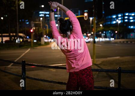 Rear view woman stretching before running