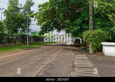A Street scene in downtown Port Gentil, with Vehicles parked beside the Storm Drains on a quiet residential road. - Stock Photo