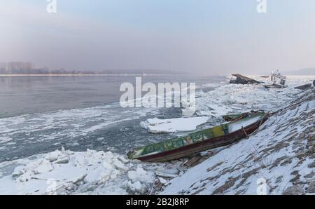 Small fishing boats trapped on frozen river Danube and many ice cubes, Belgrade Serbia, with the sinking float in the background - Stock Photo