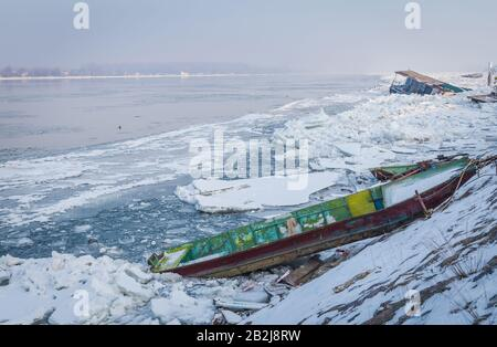 Boats trapped on the bank of the frozen river Danube, with the sinking float in the background, winter 2017 - Stock Photo