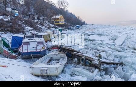 Destroyed boats on a frozen Danube river with lots of ice cubes near Belgrade, Zemun, Serbia - Stock Photo