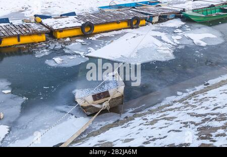 Small fishing boats trapped on frozen river Danube port and many ice cubes, Belgrade Serbia - Stock Photo