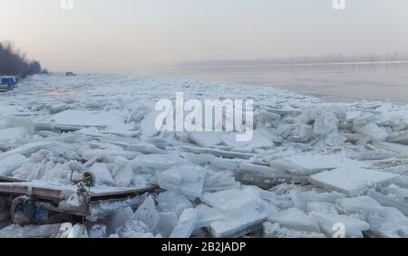 Lots of ice cubes on the Danube river with the trapped fishing boats, Belgrade Serbia - Stock Photo