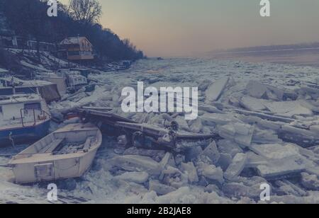 Destroyed boats on a frozen Danube river with lots of ice cubes and fantastic sunset near Belgrade, Zemun, Serbia, haze effect - Stock Photo