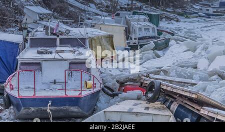 Many destroyed boats on a frozen Danube river with lots of ice cubes near Belgrade, Zemun, Serbia - Stock Photo