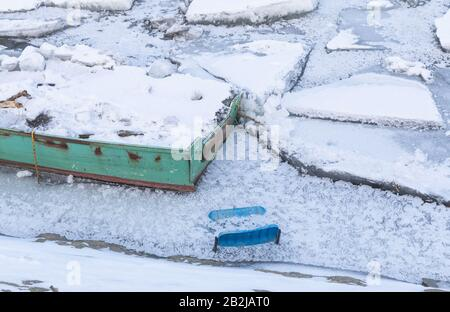 Part of small fishing boats and plastic chair trapped on frozen river Danube and many ice cubes, Belgrade Serbia, - Stock Photo