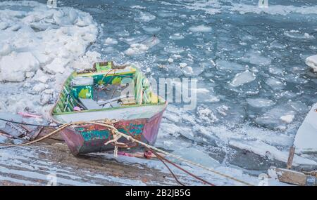 Small multicolor fishing boats trapped on frozen river Danube and many ice cubes, Belgrade Serbia, - Stock Photo