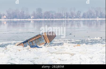 Small fishing boats trapped on frozen river Danube and many ice cubes, Belgrade Serbia, - Stock Photo