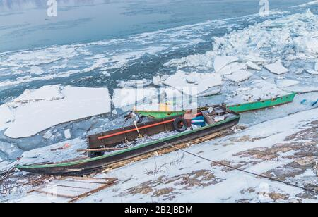 Two multicolor fishing boats trapped on frozen river Danube and many ice cubes, Belgrade Serbia, - Stock Photo