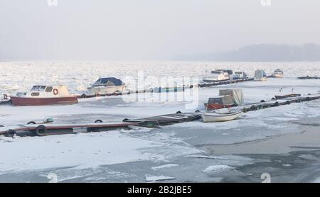 View of the frozen river port with trapped small fishing boats on river Danube, Belgrade Serbia - Stock Photo