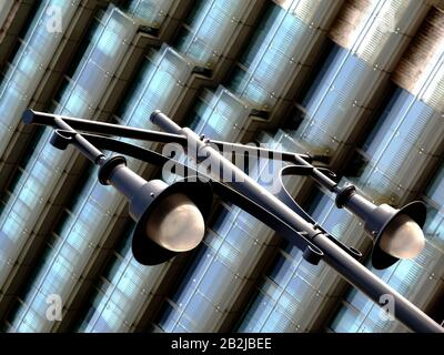 view of old vintage style street lamps on skinny tall steel posts and large glass lens covers and stylish glass exterior corridors of hotel building - Stock Photo