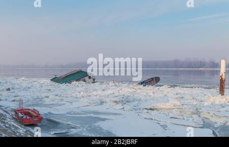 Wooden house and two boats trapped on the frozen river Danube, near the city of Belgrade, many parts of ice, with fantastic river and sky scape - Stock Photo