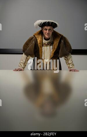 King Henry VIII standing at table in conference room - Stock Photo
