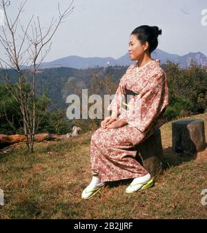 1960s, historical, a japanese lady sitting on a hillside wearing the traditional female costume, the kimono. Normally made from silk, the dress has large sleeves and go from the shoulders down to the heels. They are tied with a wide belt, an obi. In contrast to western culture where costume was designed to emphaise a woman's figure, ie, the corset, the Kimono conceals a woman's bodyline so showing the difference between the Western and Asian cultures. The Kimono in the picture is possibly a Furisode, which are made in light colours with flowers for an association witth youth and femininity. - Stock Photo