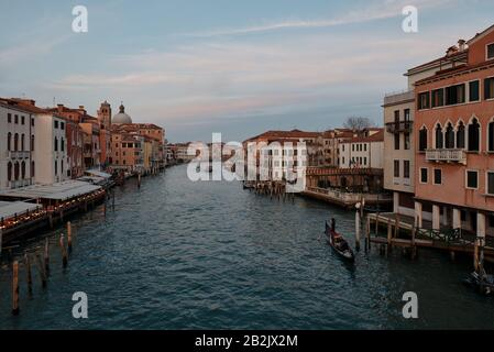 Venice, Veneto/Italy - February 16 ,2020: View over the Grand Canal in Venice and a gondola crossing the grand canal during sunset - Stock Photo
