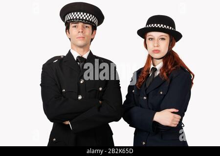 Portrait of confident police officers with arms crossed against white background - Stock Photo