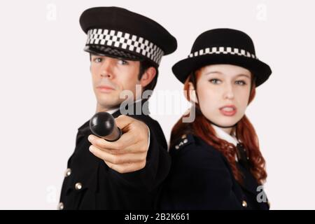 Portrait of confident police officers against gray background - Stock Photo
