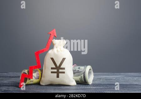 Yen yuan money bag and red arrow up. Economic recovery and growth, optimistic forecast of economic rise. Market stability. Influx of investment and ca