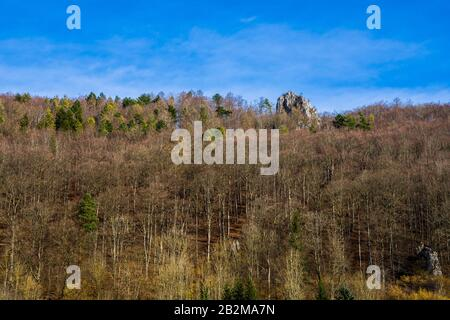 Germany, Beautiful colorful tree tops of forest in swabian jura nature landscape surrounding white rocks with hikers sitting on top on sunny day - Stock Photo