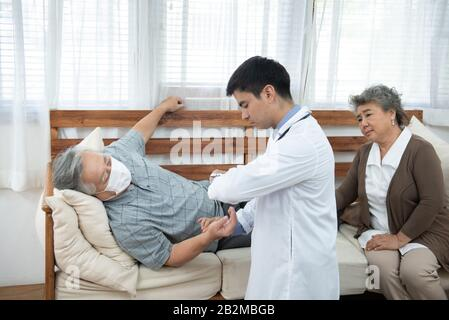 Asian senior elderly old man with mask on lying on sofa while young caucasian  doctor sit on knee check his heart beat and old senior woman sit beside - Stock Photo