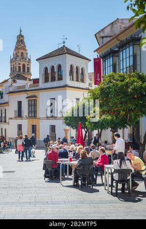 In view of the Bell Tower of the Mezquita a street cafe in Plaza Agrupación de Cofradías in Córdoba, Andalusia, Spain - Stock Photo