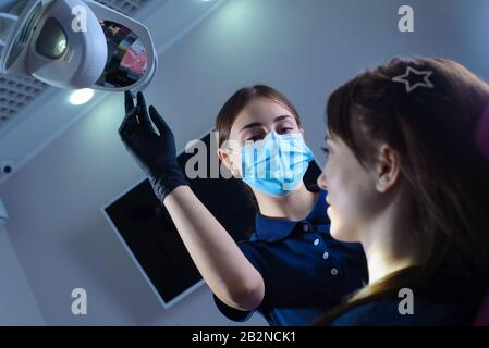 Portrait of executive dentist holding in his hand a clipboard and consulting with beautiful patient at dentist office. view from below. Dentist doctor - Stock Photo