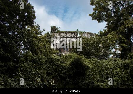A low angle shot of an ancient weathered building surrounded by green trees under a cloudy sky - Stock Photo