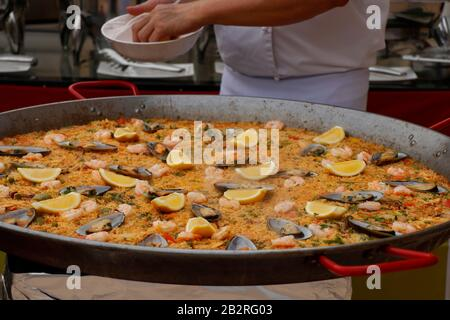 chef cooking Spanish paella in outdoor area - Stock Photo