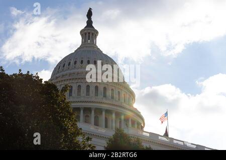 United States Capital Dome seen behind trees on a sunny afternoon, the American flag waving in the wind. - Stock Photo