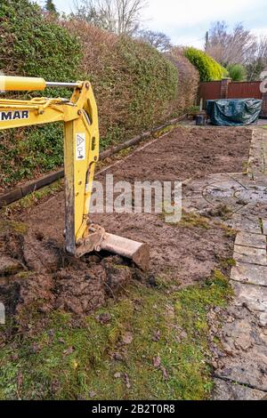 CARDIFF, WALES - JANUARY 2020: Bucket and arm of a mini excavator digging up the lawn in the back garden of a residential property - Stock Photo