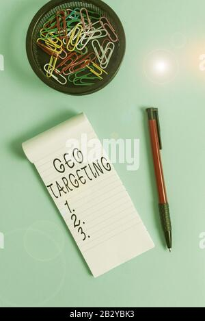Conceptual hand writing showing Geo Targeting. Concept meaning method of determining the geolocation of a website visitor Notebook and stationary with - Stock Photo
