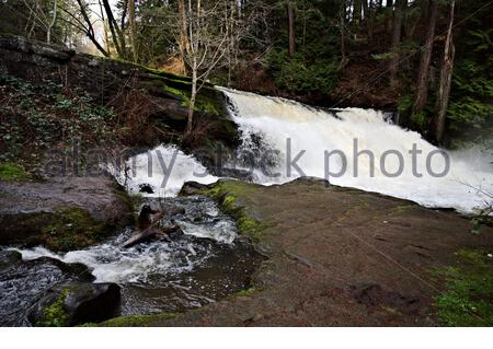 Side view of waterfall with large volume of water gushing over the ledge and little creek feeding into main river system along footpath - Stock Photo