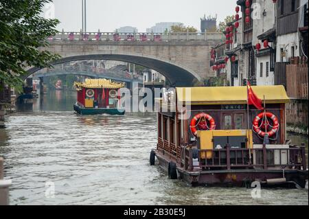 Wuxi China - October 2019: Colourful barges sail through a traditional Chinese water town, in Wuxi ancient city, Jiangsu Province, China. - Stock Photo