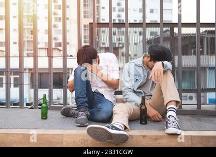 Two young men drunk and sit sleeping on street with bottle of beer in unhappy.