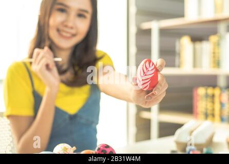Young beauty happy asian woman wearing bunny ears handmade painting on colorful Easter egg by art design paintbrush with decorative style.