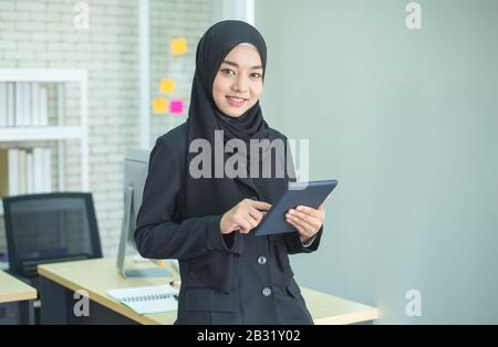 Young muslim asian female businesswoman using graphics tablet while working with computer at studio or office. - Stock Photo