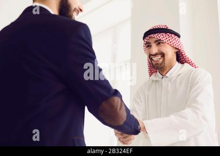 Handshake of arabic and european businesspeople in office.