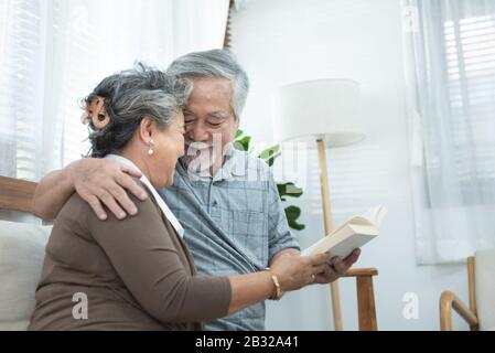 Elderly senior asian couple sitting on sofa reading book together at home.Retirement grandmother and grandfather spend time together at house.
