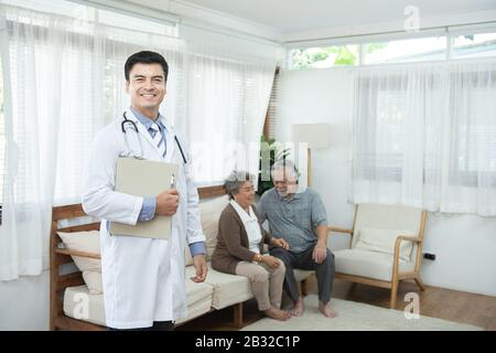 Young handsome caucasian male doctor standing hand holding document file look at camera with smile and two elderly old senior asian couple sit on sofa
