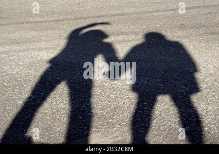 Series of silhouettes of young lovers. Series 2. Shadow of lovers hand in hand at sunset. The guy holds the girl with one hand, he raised his second o - Stock Photo