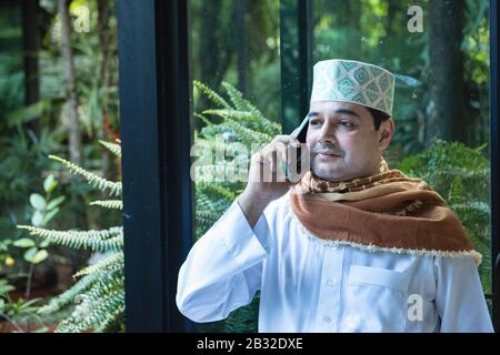 Middle eastern Emirati man in traditional clothing called kandura sitting on chair in coffee shop and talking with his mobile.Smart communication - Stock Photo