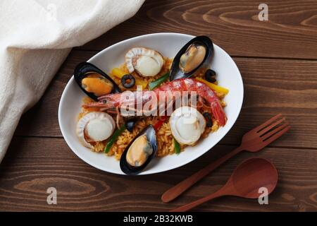 seafood paella rice closeup isolated on wooden table Stock Photo