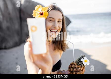 Beautiful smiling girl with hair flower showing tube with sunscreen lotion while resting with exotic summer cocktail on the beach. Sun protection concept for skin