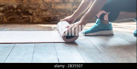 Closeup hands sporty woman rolling unrolling mat. - Stock Photo