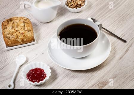 Breakfast with coffee, bread and jam on a white wooden table - Stock Photo