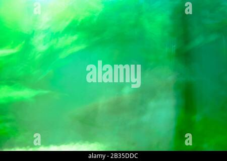 Abstract green reflection glass with water. Blurry greenish reflection in a small tank