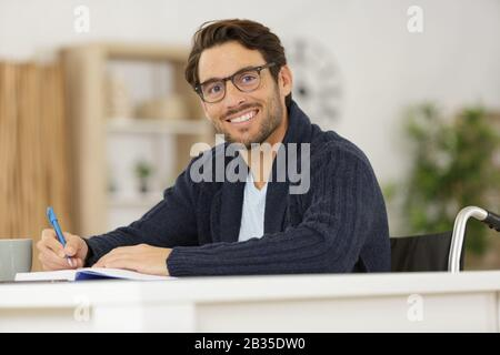 disabled young man studying at home - Stock Photo