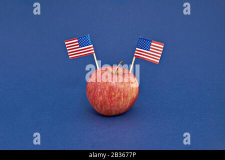 Red apple with two flags of USA on blue background. Greeting card to celebrate Happy Presidents Day, Flag Day of America, Labor Day or election Day, Independence - Stock Photo