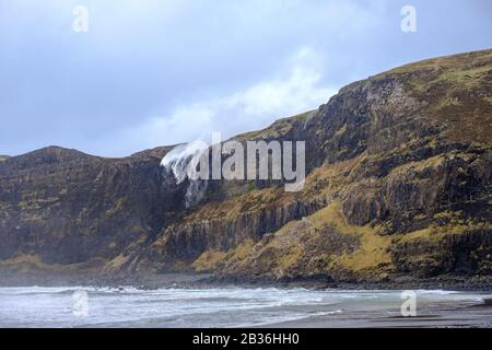 Waterfall at Talisker Bay, Skye, Inner Hebrides, appearing to flow upwards due to strong storm winds - Stock Photo
