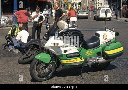 London Ambulance service motorcycle paramedic & police  assist motorbike courier rider lying in road traffic accident street scene London England UK - Stock Photo
